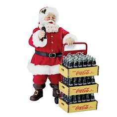 Add a touch of nostalgia to your holiday decor with this 10.5-inch Coca-Cola Santa with delivery cart set of 2 pieces from Kurt Adler. Santa Claus is featured here in his signature red and white suit. He is holding a bottle of Coca-Cola is his hand. Included is a cart carrying three large cases of Coca-Cola bottles.