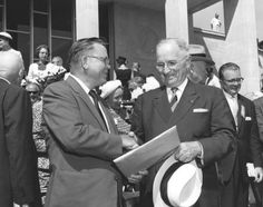 Former President Harry S. Truman (right) shakes hands with Archivist of the United States Wayne Grover (left) during the dedication ceremonies for the Harry S. Truman Library, July 6, 1957.