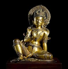Bodhisattva Nepal, circa 16th century A gilt copper repoussé figure of a bodhisattva. Reclining into 'royal ease' while displaying the gesture of teaching with an attentive gaze.