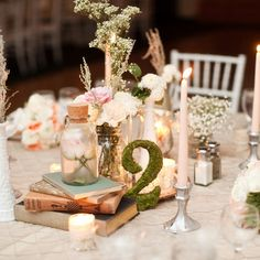 Collect bottles, jars and vintage books and decorate the tables along with candles, moss table numbers and soft pastel florals.
