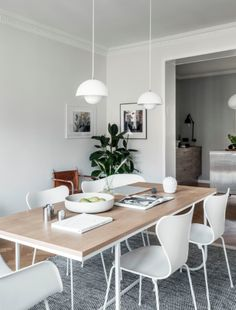 simple dining space, white chairs, wooden table top, grey marl rug, plant, white pendent lights