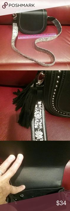"NWT Black Embroidered Guitar Strap Bag Final Price This is a black bag with silver studs, 2 tassels, and a removeable white stitched embroidered guitar strap. Use as a crossbody or on the shoulder.  The bag measures about 8"" long, by 7"" high.  Inside is a small zippered section on one side,  the outside back is plain.  This is a final price item but you can still save 15% when you bundle. new directions Bags"