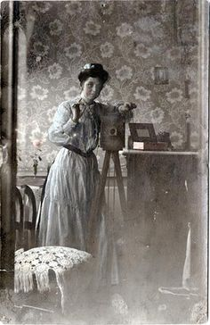 "A young woman in a tinted blue dress and her camera are reflected in a large mirror. The left side shows a double image of a chair and the wall paper in the beveled edge of the mirror. This real photo postcard is marked ""Rébublique Française"" and ""Carte Postale""."