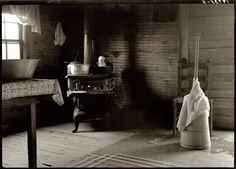 July 1939. Corner of a sharecropper's kitchen showing stove and butter churn. Person County, North Carolina. by Dorothea Lange.