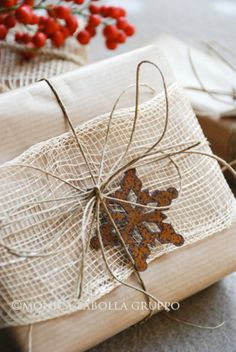 Brown paper packages tied up with string, burlap and a rusty snowflake ornament