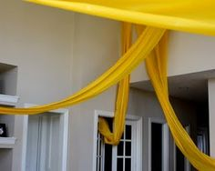 weaving a 100ft roll of yellow plastic table coverings throughout the house for a Rapunzel Birthday party...HOW AWESOME