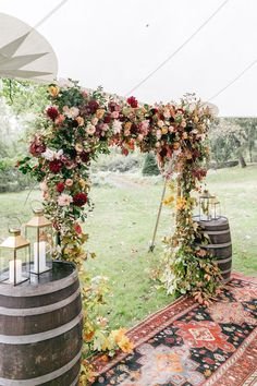 A lush fall wedding arch with blush, burgundy and orange blooms plus fall leaves and a vintage carpet for a boho vibe. Fall Wedding Arches, Wedding Ceremony Flowers, Wedding Flower Arrangements, Autumn Wedding, Wedding Bouquets, Floral Arrangements, Rustic Wedding, Wedding Day, Ceremony Arch