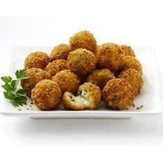 Arborio rice balls with spinach and Parmigiano-Reggiano and a cube of mozzarella cheese inside are rolled in seasoned panko bread crumbs, then deep fried until golden brown for an impressive and delicious appetizer.