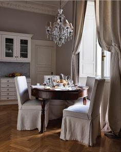 source: Stefania Di Girolamo      Chic European dining room with gray walls paint color and elaborate crown molding millwork. Soft gray linen curtains window panels and herringbone pattern wood floors. Round dining room table paired with linen slipcover slipper chairs. Dining area set in front of bi-fold doors to balcony and crystal chandelier with gray shades.