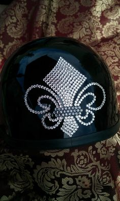 Bling your Motorcycle Helmet to match your ride. We use Genuine Swarovski Crystals for the best sparkle and shine. Create your own design for your helmet or let us do it for you. Sparkle up your day with Custom Bling by Ricci~    Show off in this elegant Fluer-De-Lis Lady's Blinged out Motorcycle Helmet.  You won't be missed in this one!