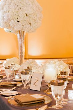 The combination of gold, purple and white is incredibly regal for a formal wedding reception. By Erin Hearts Court