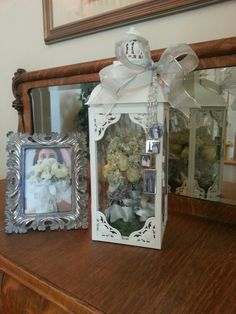 Fun idea for displaying dried flowers from my daughter's wedding bouquet. The  photo charms hanging on the front hold the wedding pictures of her grandparents and parents. They were originally attached to the bouquet.