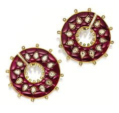 PAIR OF INDIAN RUBY, DIAMOND AND ENAMEL EAR CLIPS.  Each of circular-form, highlighted by numerous pear-shaped rose-cut diamonds, amid a calibré-cut ruby-set background, the reverse embellished with red, green and white enamel floral motifs, mounted in 18 karat yellow gold.