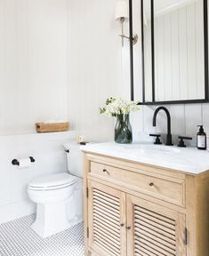 Light wood vanity and black accents in a bathroom