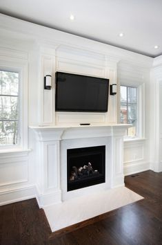 wooden home decor This wooden mantle, with a marble hearth, are a brilliant white color for a modern touch on a fireplace. The TV creates the perfect middle ground for modern and luxurious decor. Tv Over Fireplace, Fireplace Built Ins, Faux Fireplace, Fireplace Remodel, Living Room With Fireplace, Fireplace Surrounds, Fireplace Design, Fireplace Ideas, Farmhouse Fireplace
