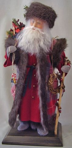 A Canadian North Woods Santa  -   This serious fellow is dressed in a buttoned, deep red wool coat. His grey suede leather boots are trimmed in fur. He keeps warm in a long tartan vest also trimmed with dark grey fur, and a fur cap. Over his shoulder is a sack loaded with toys and treats, (which he also carries in his vest pocket), for good boys and girls. A little bird stops by on top of his natural wooden staff.