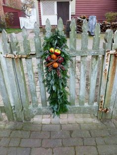 This colonial Christmas welcome is perfect for a wooden gate ~ made of greenery, small apples, dried pomegranates and oranges, pinecones, and cinnamon sticks! — at Colonial Williamsburg. Source Facebook