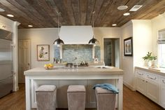 wood ceiling, white cabinets, wood floors, neutral plain countertop