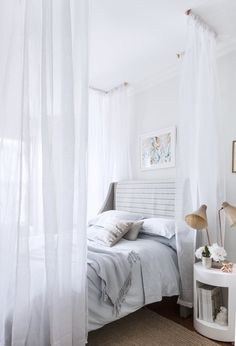 Four corners is really all you need to make a canopy bed. Here, brass piping is affixed to the ceiling, and gauzy white fabric is hung from ...