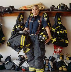 Stock Photo : Female firefighter in front of gear rack in station house, portrait