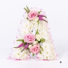 Tribute Letter - Pink. A tribute letter made using a mass of white double spray chrysanthemums edged with fern and leather leaf, with feature sprays of pink roses, white spray roses and pink veronica.