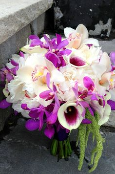 White and fuchsia orchids, white peonies and picasso calla lilies are a colorful bouquet combination.