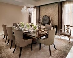 The formal dining room is the perfect place to entertain and host intimate dinner parties. From the embroidery on the chairs to the delicate yet opulent chandelier, the scheme exudes a calm decadence. The color palette is a pared back combination of soft taupes and pastel greys, which creates a smart and refined aesthetic. Designed by Katharine Pooley.