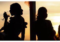 Fotografía de bodas Fotografía en color con el juego de luces del anochecer y las sombras de alguien bebiendo de una copa