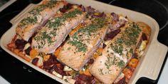 Skøn ovnret med saftige laksefileter, der steges i et fad med rodfrugter og fløde.
