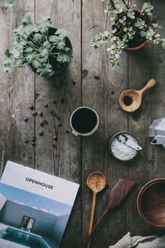 Moody flatlay using handmade wooden spoons, plants and coffee on top of an old rustic wooden table.