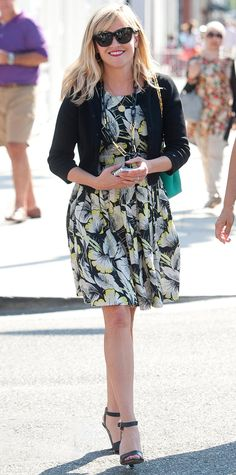 Reese Witherspoon stepped out in a black-yellow-white floral printed frock that she topped with a black cardi, a jade Roland Mouret handbag, and ankle-strap heels. #InStyle