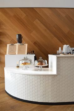 St. Frank The curved bar is the focal point of the coffee shop. White corian and ceramic tile offset the oak flooring and wall treatment. Glass Cake Stands (?) too generic - could not find Photo credit: Leslie Santarina