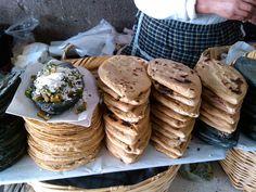 Tlacoyos rellenos de haba, de frijol y requesón en maíz azul y blanco con nopales encima con salsa, y queso rallado.