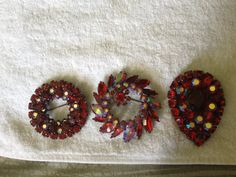 3 Japanned red brooches . All different times made. 1947-1981 was the time Sherman was open in Canada.