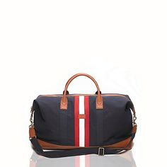 """Tommy Hilfiger men's bag. Perfect for weekend getaways, our duffle is lined to keep your gear dry and durable enough to take anything you throw at it (or in it). Finished with our signature grosgrain stripe.<ul><li>Duffle silhouette in cotton canvas with leather-like trim.</li><li>12.5"""" (H) 24"""" (L) 8"""" (W) 5"""" drop, adjustable shoulder strap.</li><li>Zip closure, lined, reinforced base, embossed Tommy insignia.</li…"""