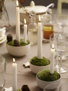 Moss & candle centerpieces: fill small bowls with floral foam, then cover with cushion moss. cut 5 cm plug wire with pliers, and push one end into the bottom of the candle, then push the candle into the moss. add pinecones or other decorations Candle Centerpieces, Christmas Centerpieces, Diy Candles, Christmas Decorations To Make, White Candles, Large Candles, Christmas Candles, Wedding Centerpieces, Wedding Decor