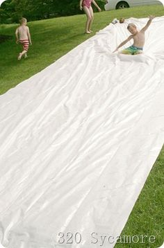Homemade Slip N Slide - Film-Gard 10 x 25, 4 Mil Plastic Sheeting, weights on the corners, No-Tears Baby Shampoo to make it slippery, and a hose