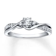 A classic round diamond at the center of this engagement ring for her is enhanced by more diamonds lining the band. Twists of 10K white gold wind around the center, adding extra style. The ring has a total diamond weight of 1/3 carat. Diamond Total Carat Weight may range from .29 - .36 carats.