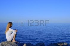 Girl sitting on the rock by the peaceful sea at sunset.