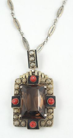 Smokey quartz pendant Theodor Fahrner circa 1930  Smokey quartz pendant with black enamel and flattened coral beads gilt over silver, original elaborate gilt chain