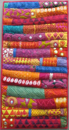 This is NOT a stack of quilts but an actual quilted wallhanging inspired by fabrics seen in New Delhi.