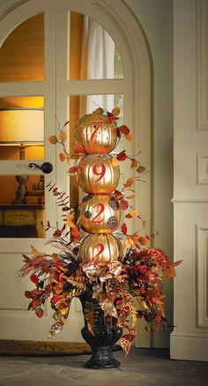 This large golden + blinged out street number pumpkin column with a  grand Autumn foliage arrangement at the base makes a HUGE impact on your home's curb appeal! (Ps. Love the doors)