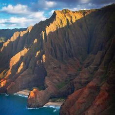 """Photo by @ChrisBickford @NatGeoTravel. An aerial view of the Honopu Valley, at the edge of the NaPali Coast on the island of Kaua'i, Hawai'i. Locally this spot is often referred to as """"Cathedrals"""", after the gothic-spire-like formations of the surrounding cliffs. This is the ultimate """"lost valley"""". It can only be accessed by swimming around the point"""