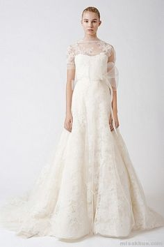 Esther  Illusion sweetheart soft a-line gown with multi-layered chantilly lace applique, sheer tulle elbow-length sleeve with floating lace, and horsehair sash at natural waist.