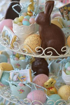An Easter table centerpiece with chocolate bunnies, candy eggs, egg cups and Easter eggs | homeiswheretheboatis.net #spring #tablescape