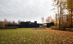 The dark, double-height volumes of this home in southern Quebec, designed by Les Architectes FABG, abstract its scale from the outside.
