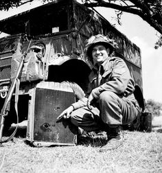 Sergeant R.A. Garbutt of the 19th Field Regiment, Royal Canadian Artillery (R.C.A.), showing shrapnel holes in the radiator of his vehicle made by a German 88mm. anti-tank gun in Normandy, France, 16 June 1944.