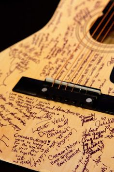 Love this guest book idea from a wedding . The couple loved music so they had guests sign a guitar!  How cool is that??  Photo by Tom K. Photography