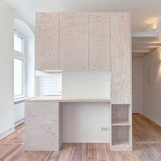 A pine unit provides a kitchen, bathroom and mezzanine level for this tiny Berlin apartment designed by local studio Spamroom and architect John Paul Coss.