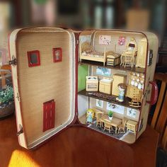 """""""EMMA HOUSE""""A full dollhouse created inside a vintage suitcase.  The house has a bedroom on the top floor, a kitchen on the middle level and a dining room on the bottom level.  The furniture is high quality timber dollhouse furniture in 1:12 scale. The doors and drawers open. A lot of the suitcase's original vintage lining paper is intact, with some decorative paper and ribbon trim around the edges to add colour and interest. There is a timber front door and windows painted burgundy to match the Painted Suitcase, Suitcase Decor, Vintage Crafts, Vintage Toys, Etsy Vintage, Vintage Suitcases, Vintage Luggage, Timber Front Door, Dollhouse Furniture"""